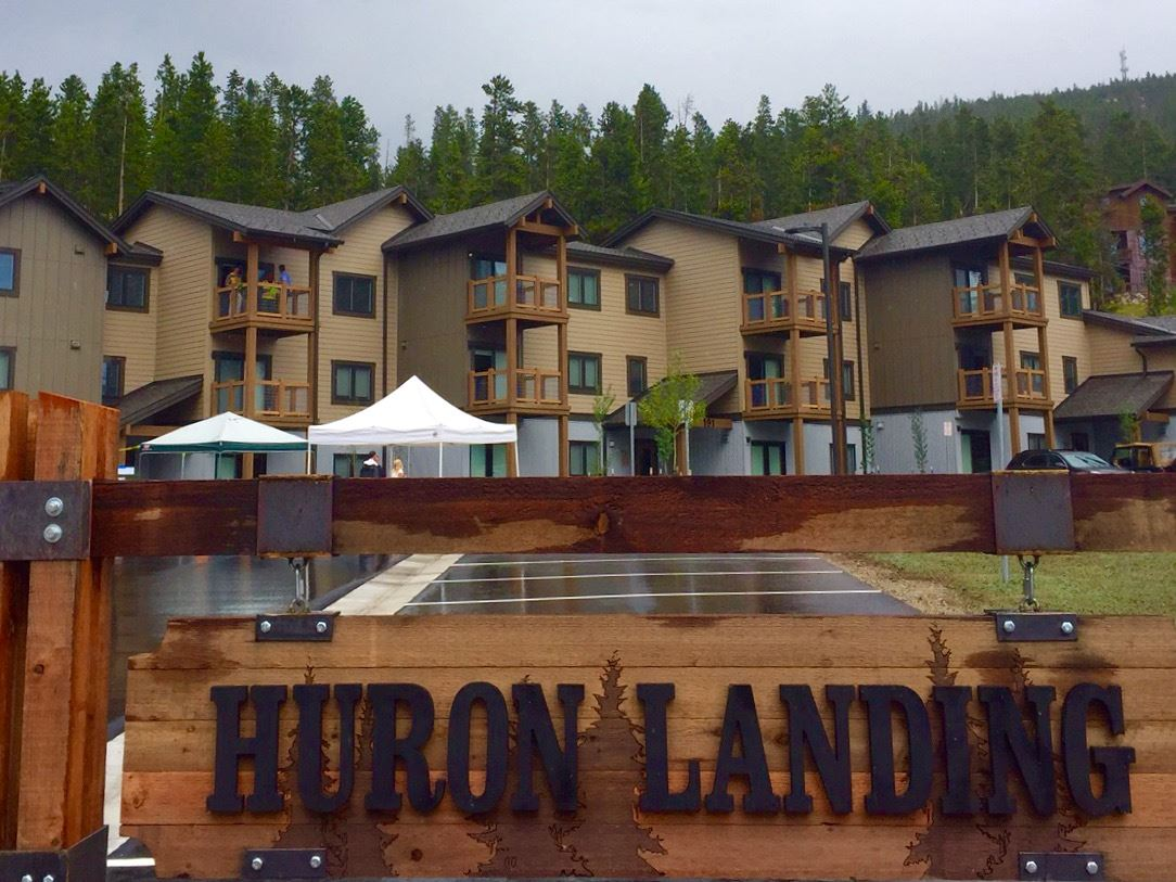 A three-story apartment building behind a sign that reads, Huron Landing.