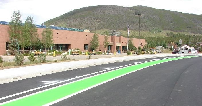 A green bicycle lane in front of the school.
