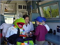 Photo of ambulance staff with children and a puppet.