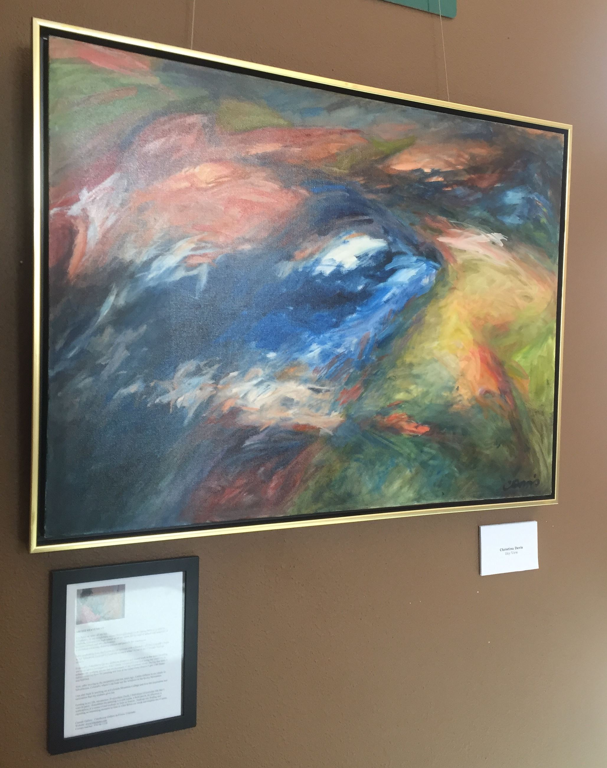 Photo of an abstract painting that includes large swaths of many colors.