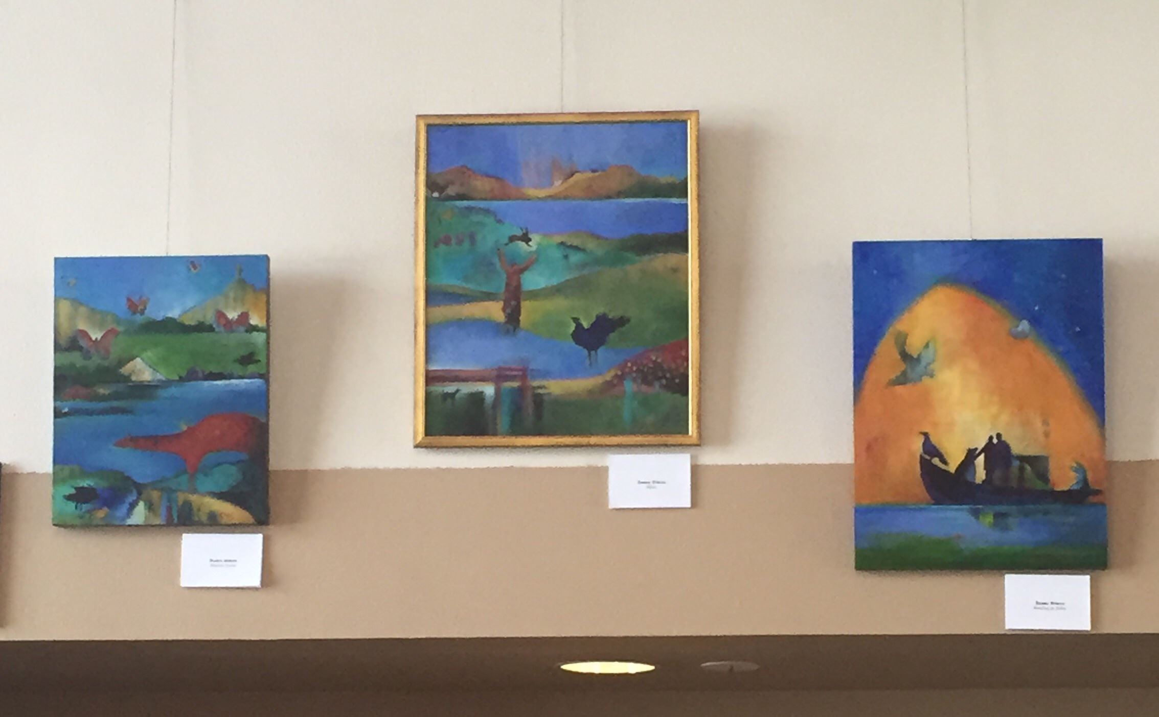 Photo of several paintings hung on a wall.