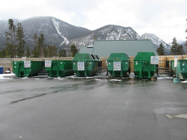 Photo of large green recycling drop-off containers.