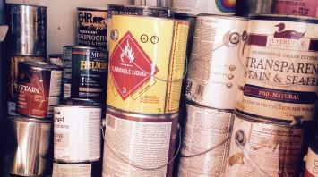 Photo of piles of old cans of paints and stains.