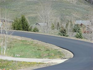Photo of a freshly paved road, with unfinished shoulders.