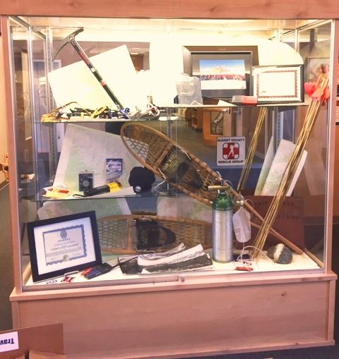 Photo of a display case containing a ski patrol jacket and other rescue gear