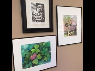 Three framed pieces of artwork hanging on a wall.