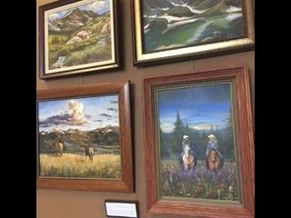 Four paintings of mountain landscapes, hanging on a wall.
