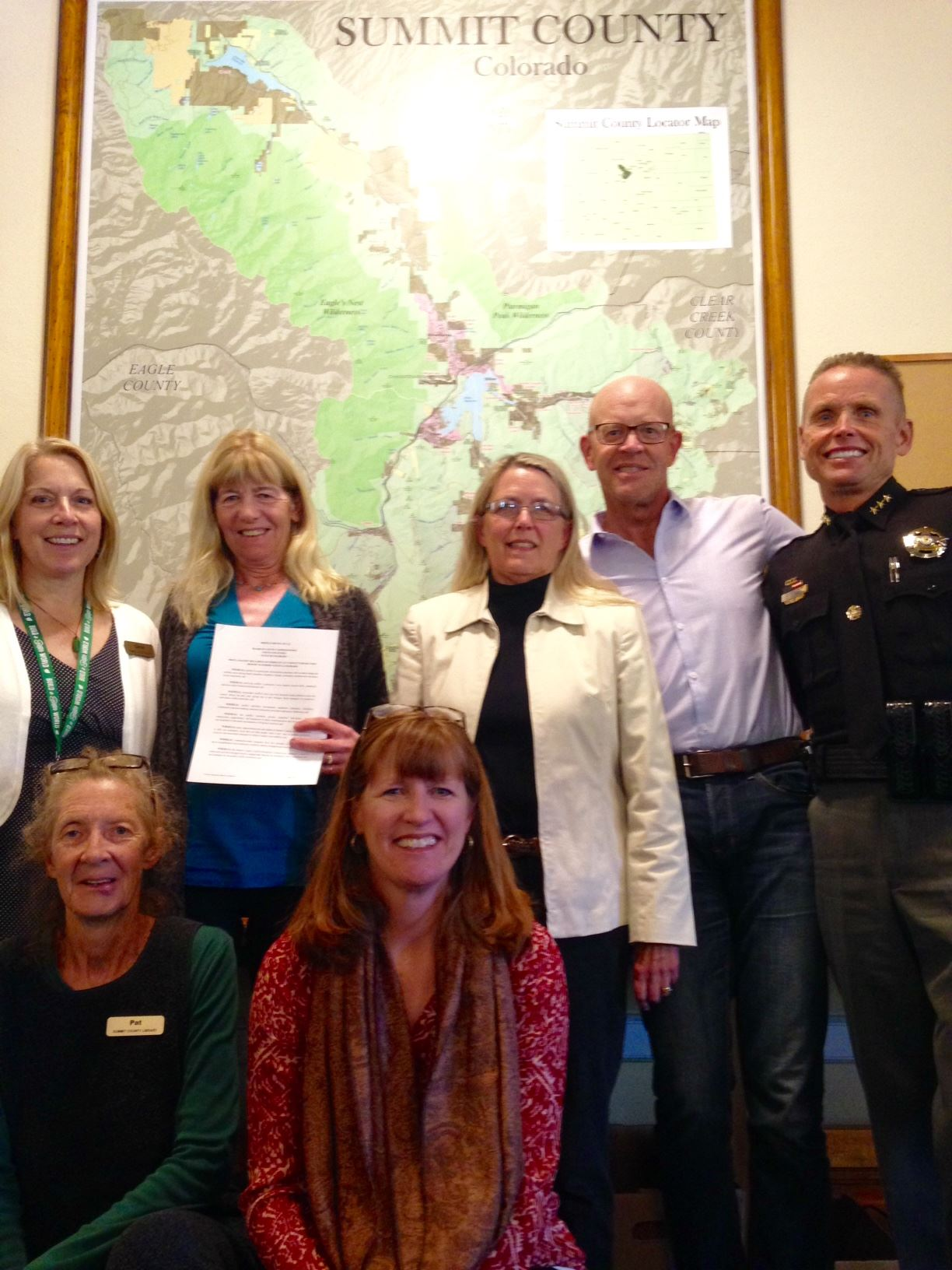 Seven community members stand with a proclamation.