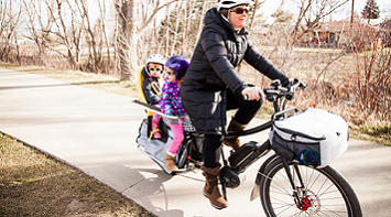 A women rides an electric bicycle with two kids on the back.