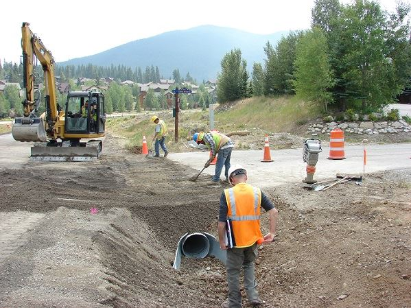 Workers installing culvert on a job site