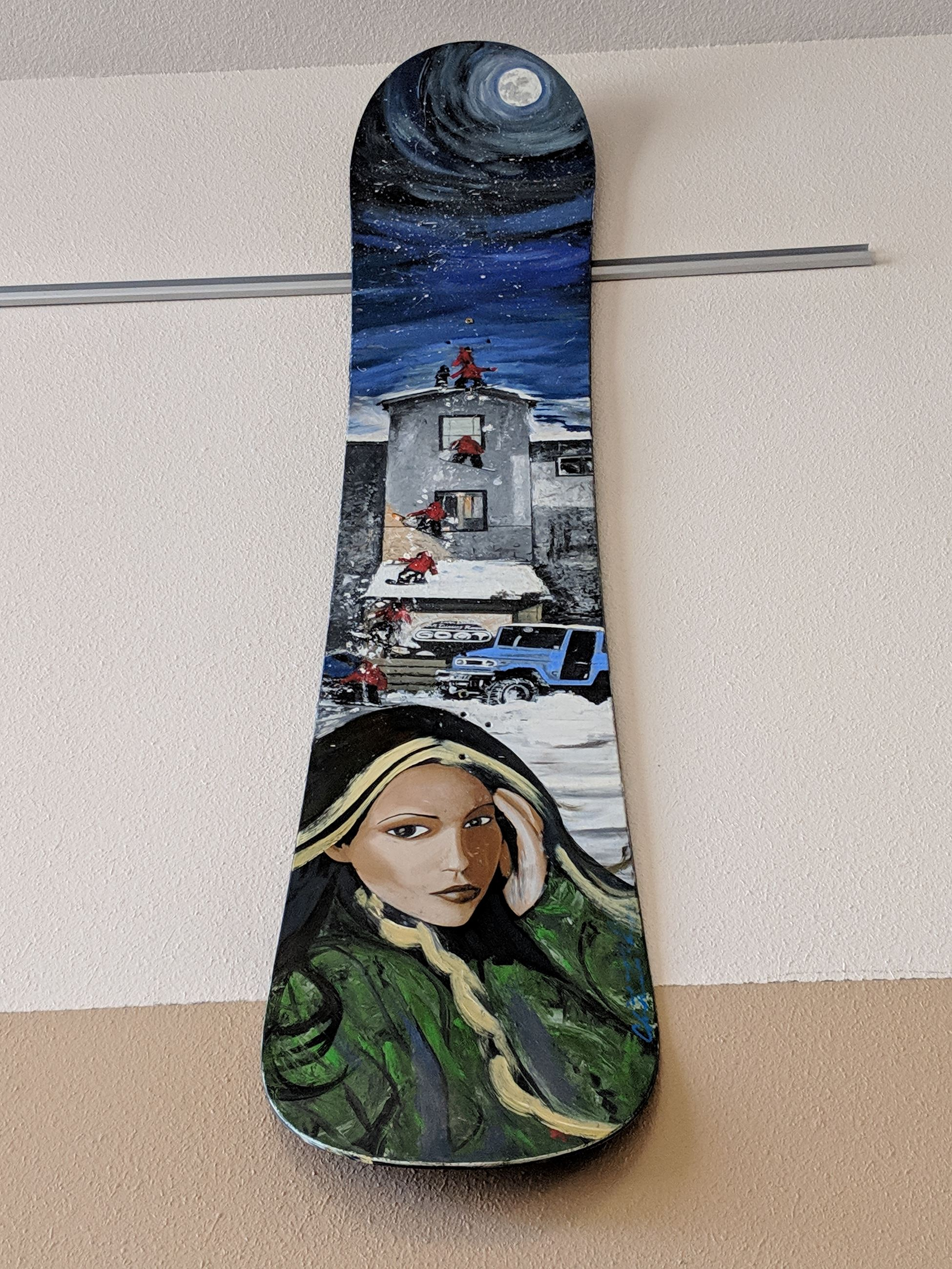 Photo of snowboard painted with images of snowboarder, house and woman
