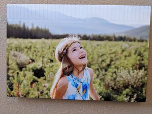 Photo of little girl looking up to sky, among young pines with mountains in background
