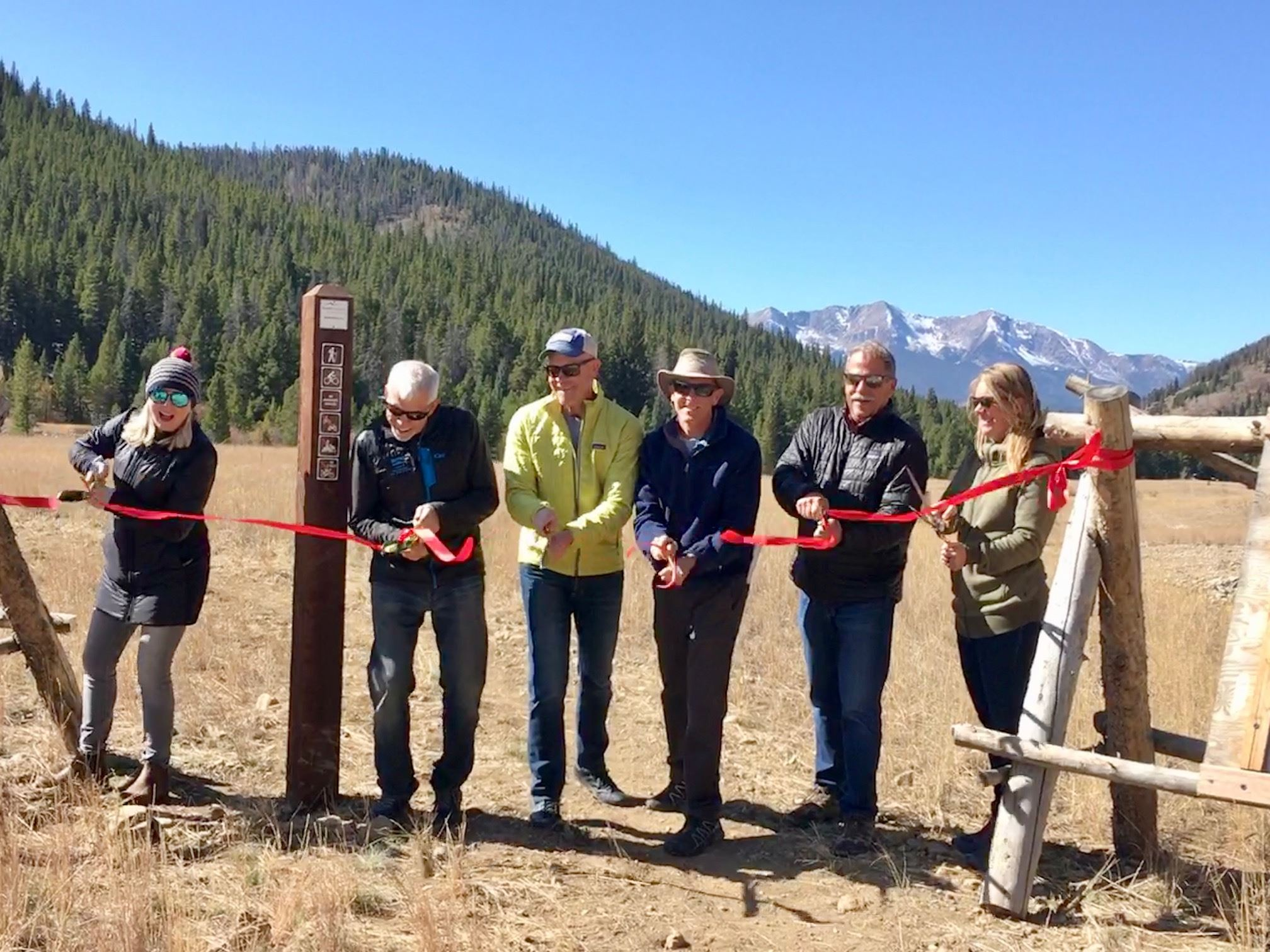 Public officials cut the ribbon at the gate to the Swan River Restoration site.