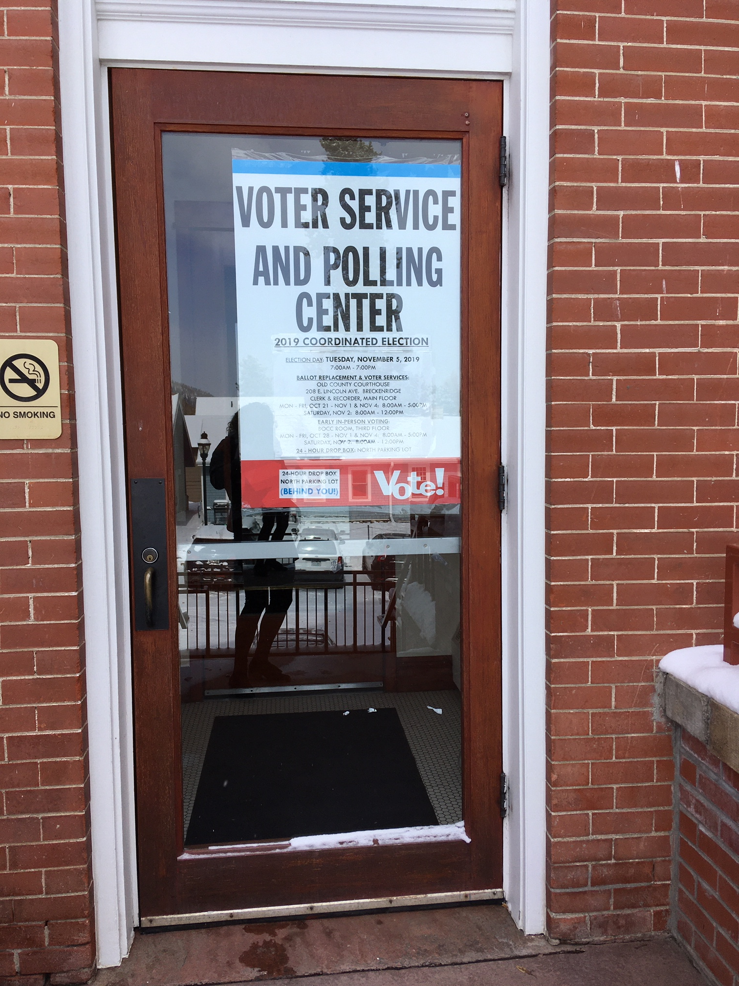 A sign on the County Courthouse door indicates the building is a polling center.