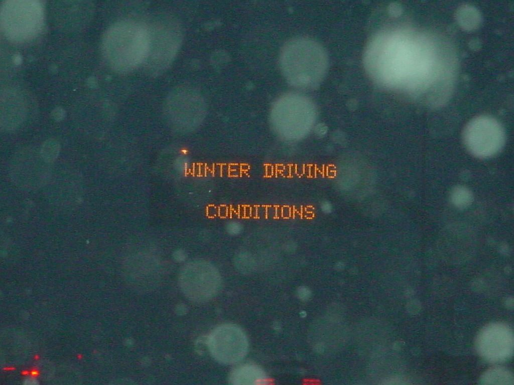 "A variable message sign on the highway says ""Winter Driving Conditions."""