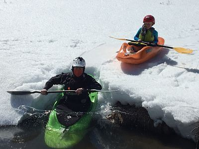 Father and son kayaking in snow