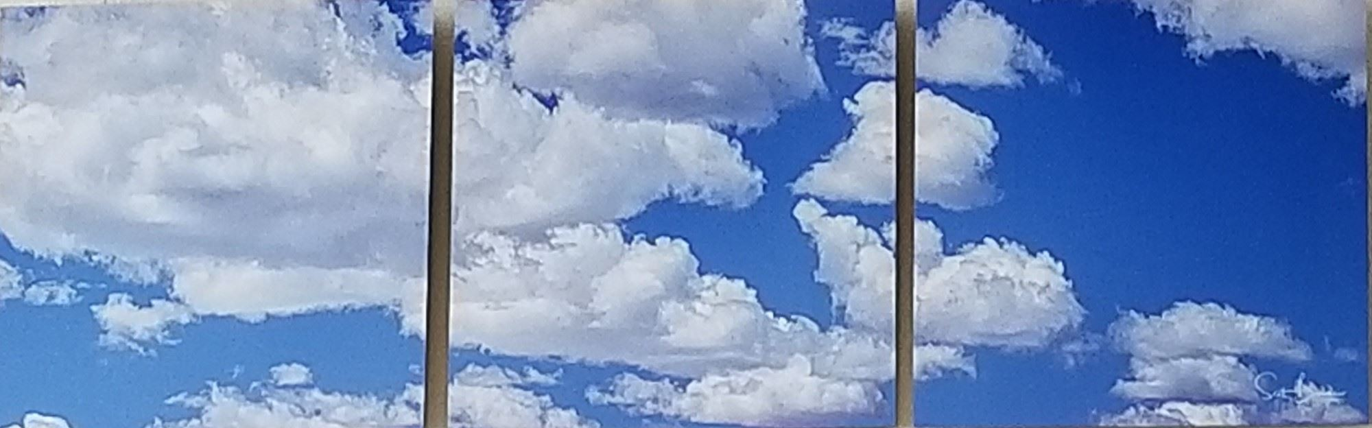 Three photos on metal of clouds