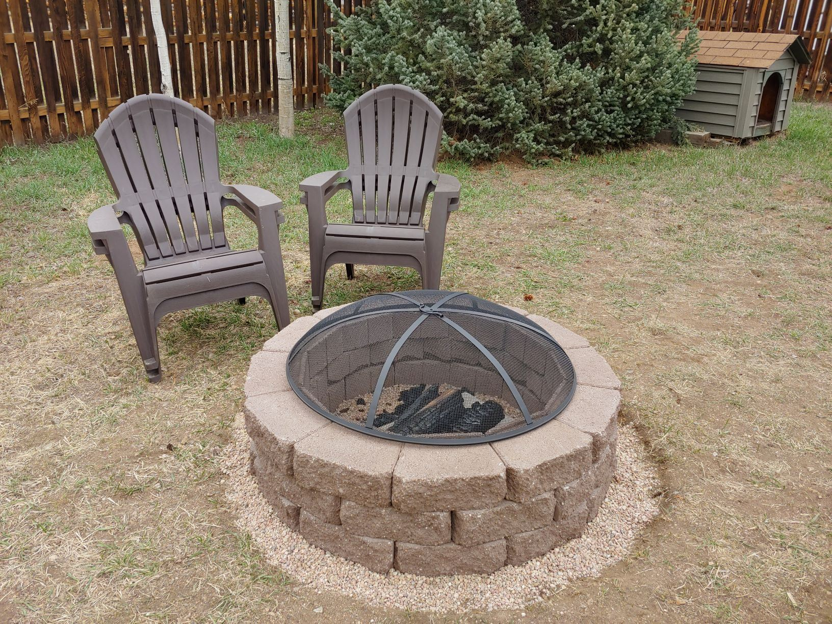 A fire device with an ember screen in a backyard.