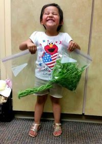 A little girl holds a bag of produce