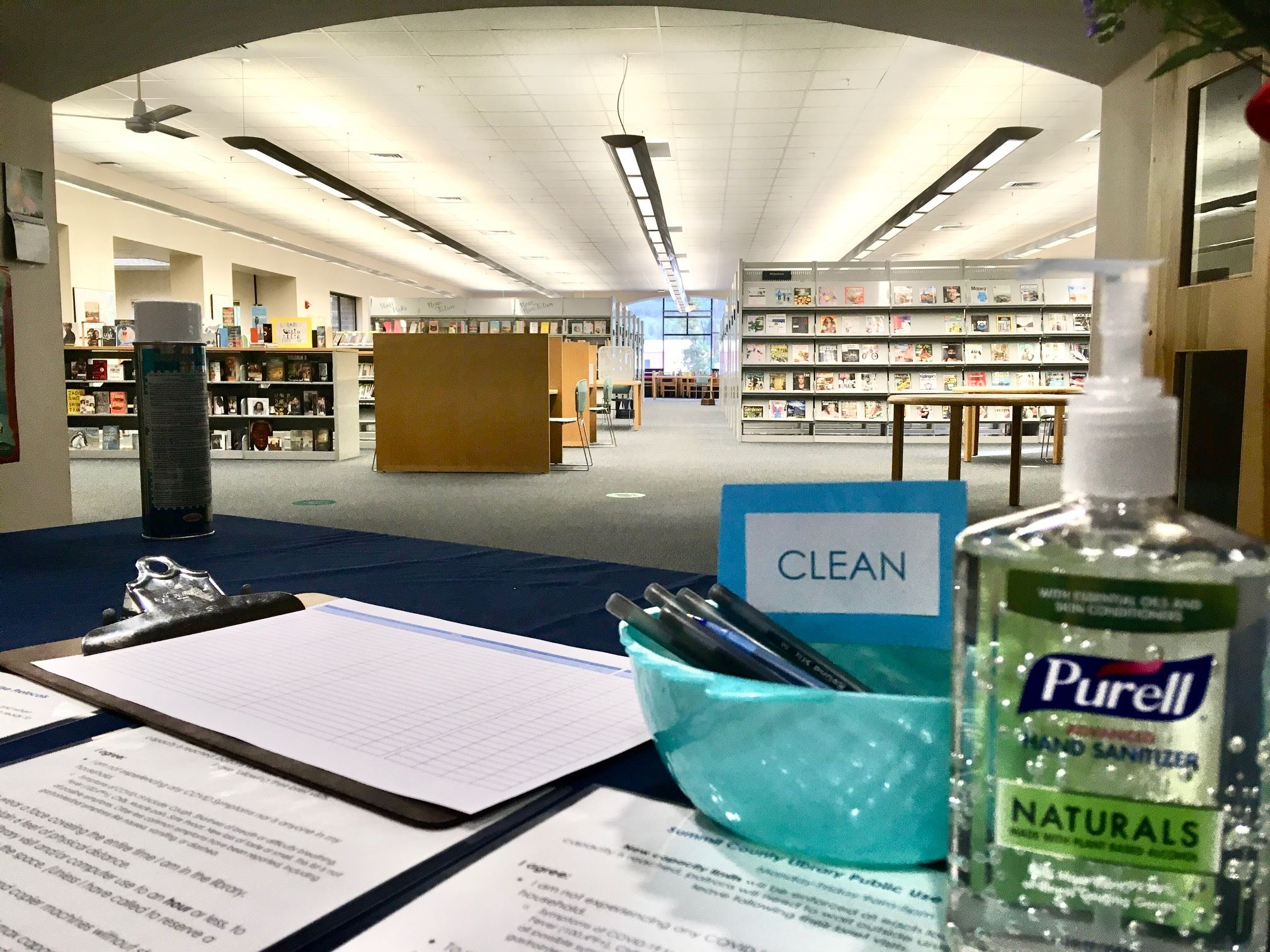 A container of hand sanitizer and a bowl of clean pens at the library entrance.