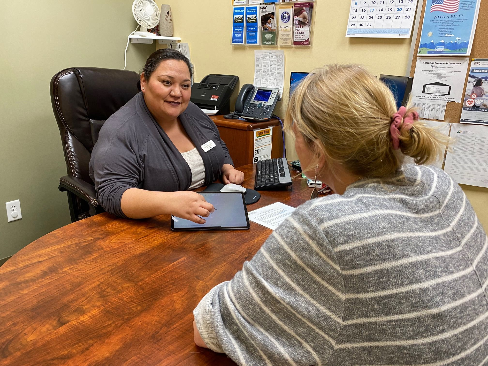 A human services worker talks with a woman in an office.