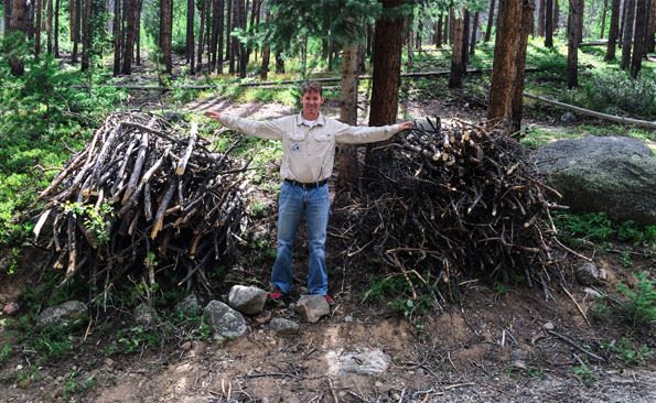 Photo of a man standing in front of two slash piles.