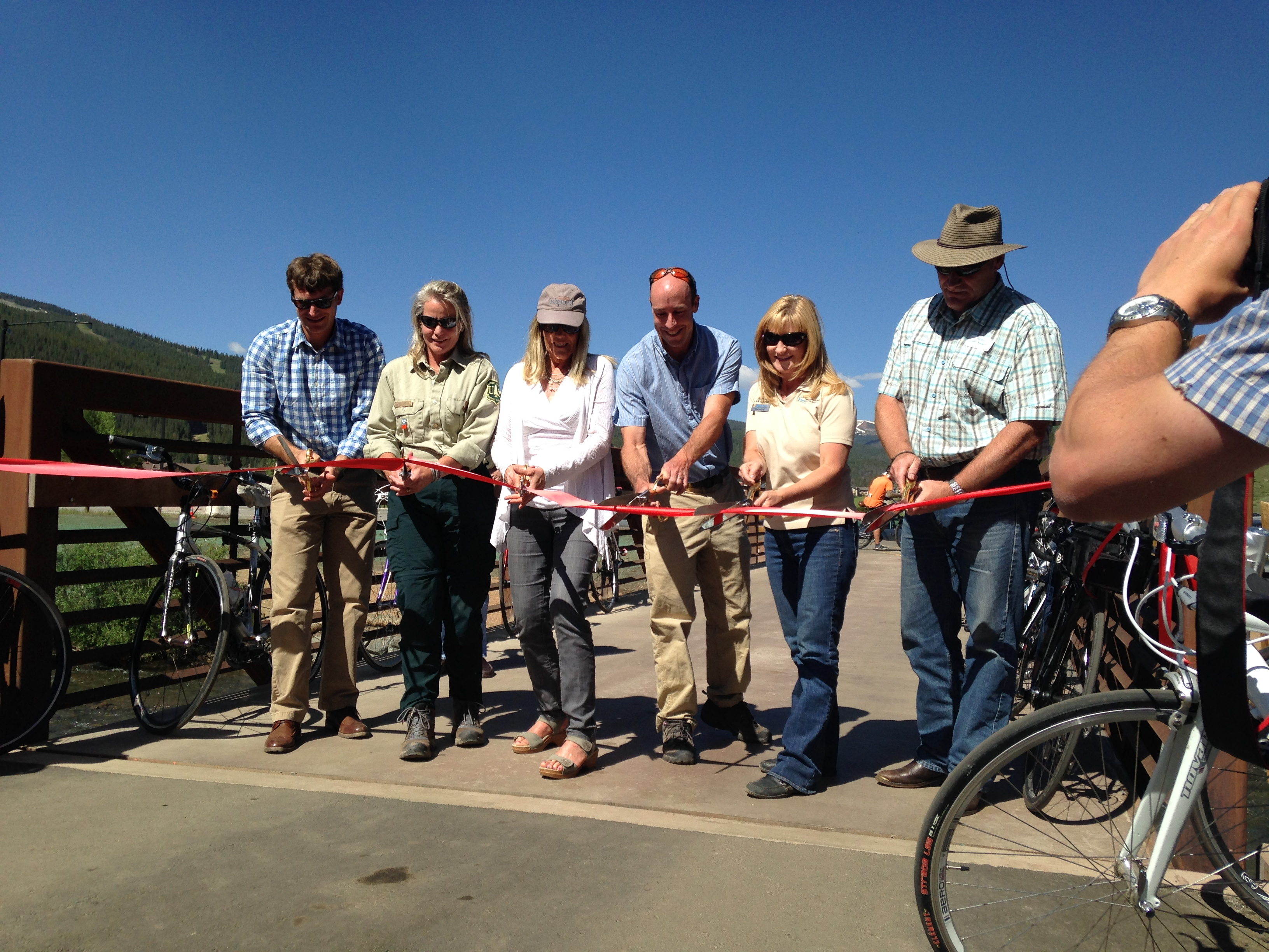 Six officials from various agencies cut a ribbon stretched across a pathway bridge.