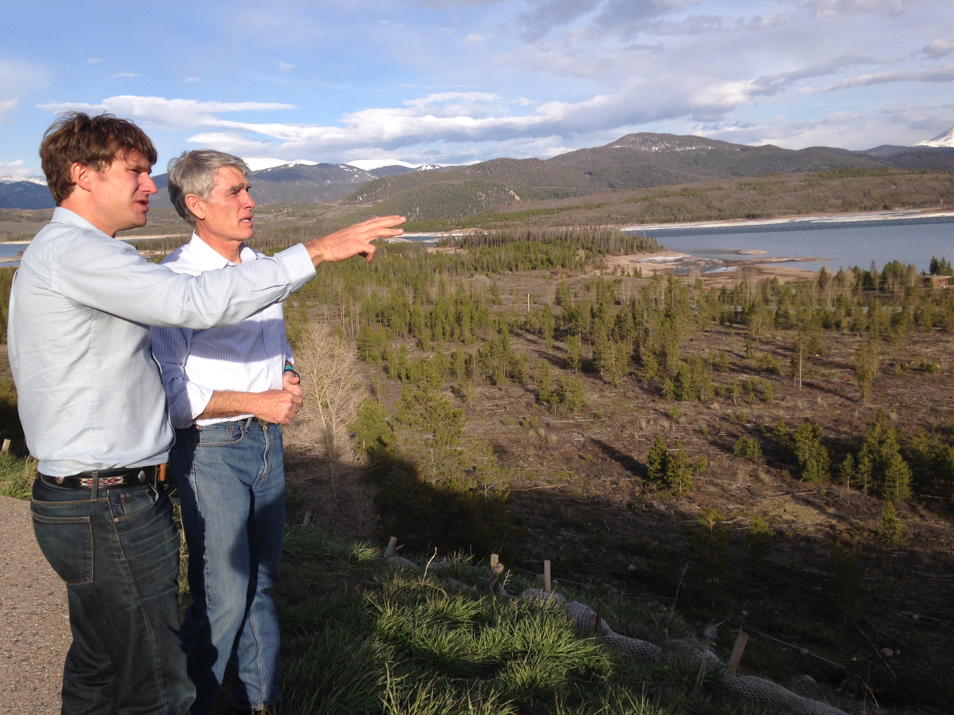 Commissioner Dan Gibbs and Sen. Mark Udall stand on an overlook, viewing a hillside above Dillon Reservoir.