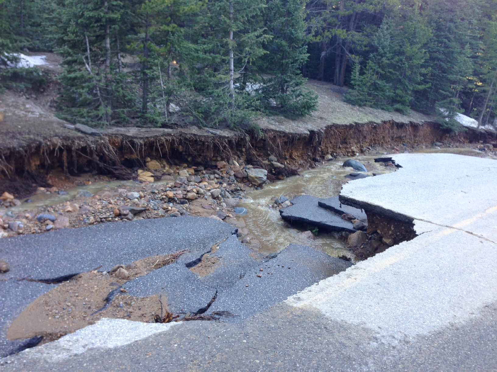 Photo of a section of road that has been undercut by flooding.