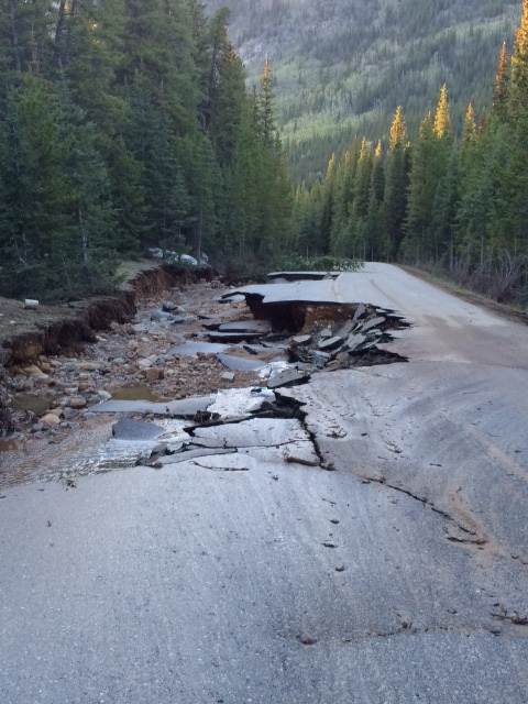 Photo of a portion of collapsed road undercut by flooding
