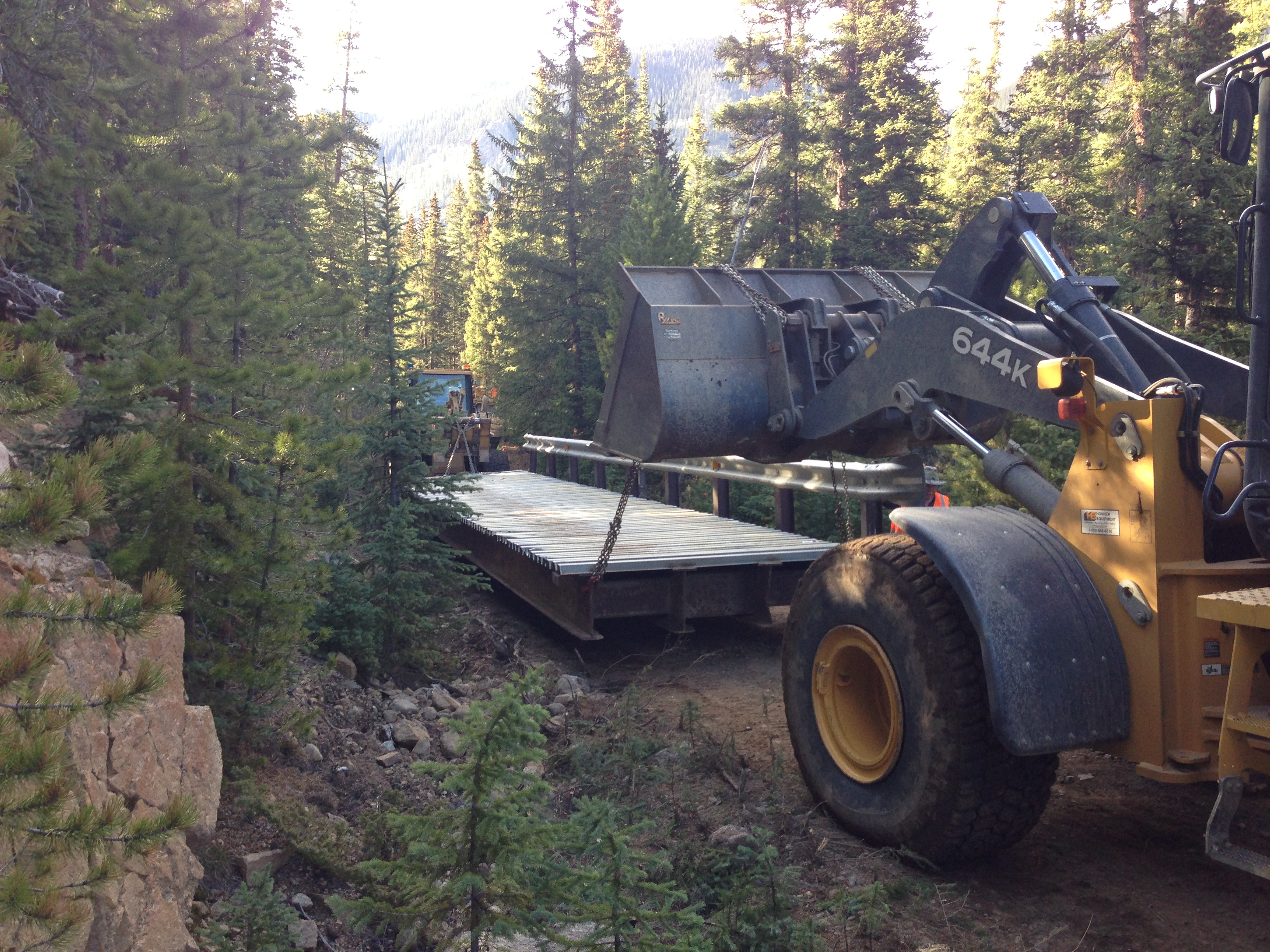 A machine transports a bridge through the forest