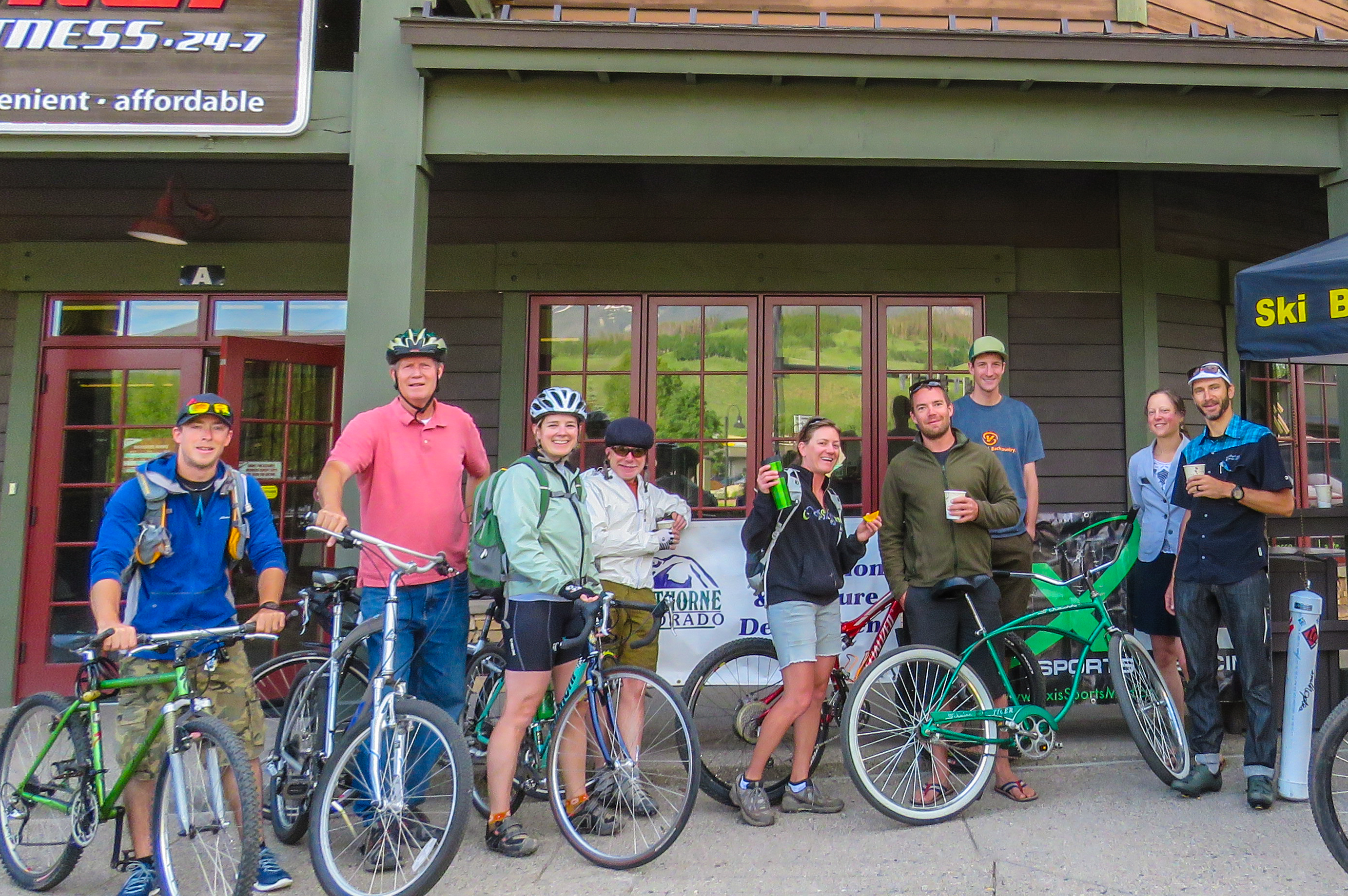 Photo of nine cyclists in front of a building, where they have ridden to work.