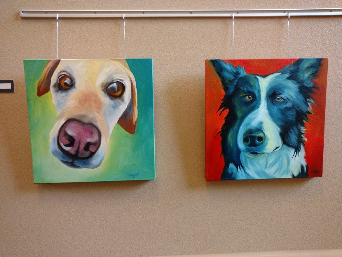 Photo of two paintings of dog faces.