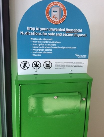Photo of a green medication drop-off box.