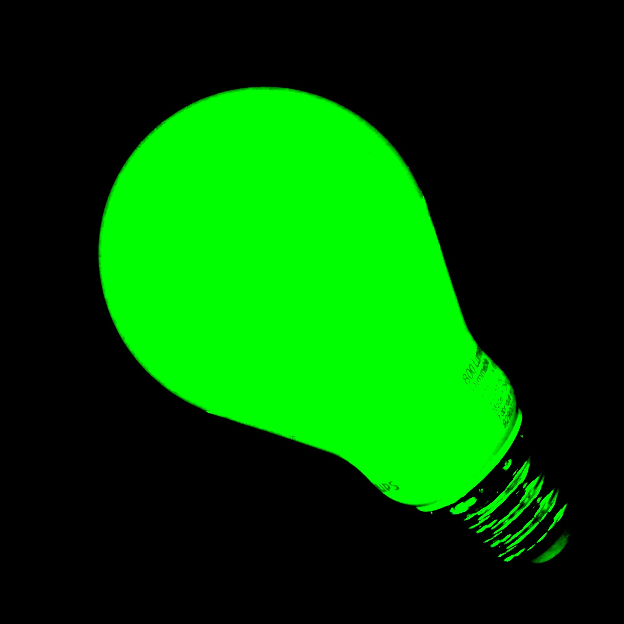 Photo of a green, glowing LED light bulb.