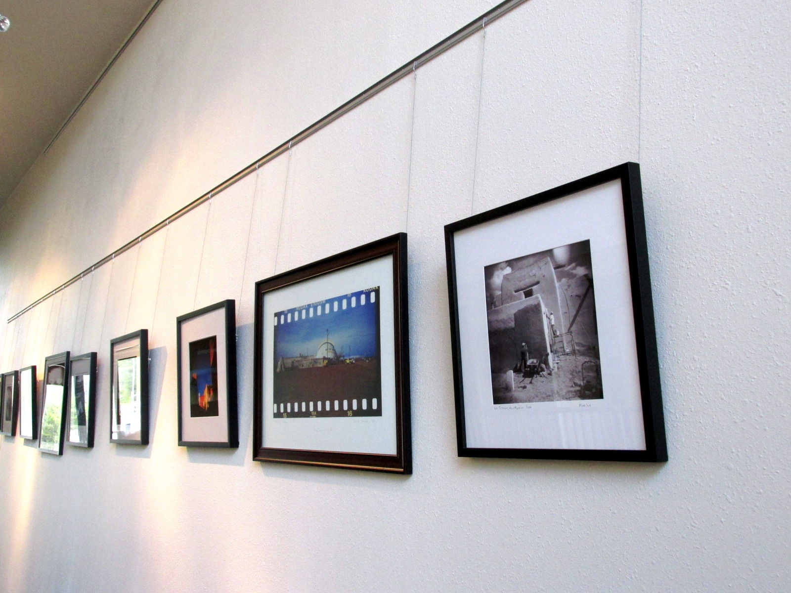 Photo of several pieces of art hanging on a wall.