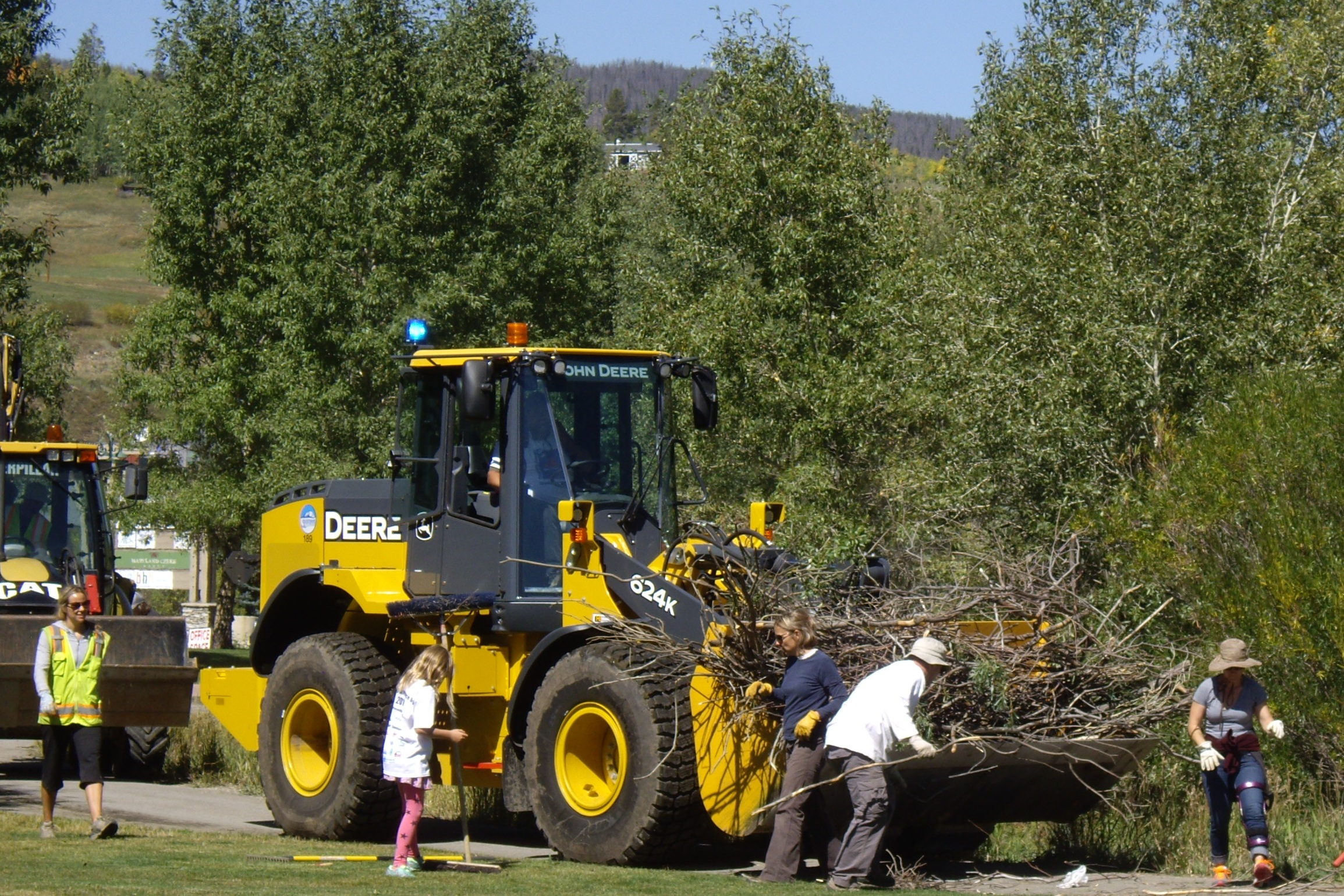 Photo of volunteers loading brush into a tractor.
