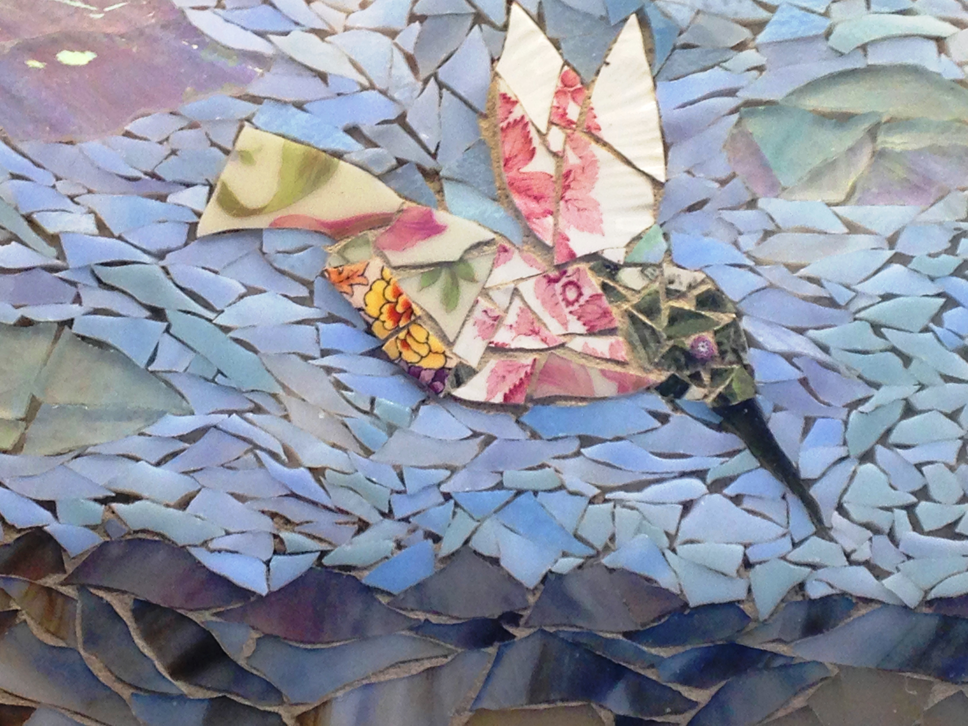 Photo of a mosaic that depicts a humming bird.