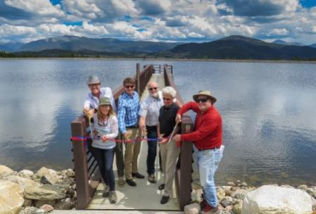 Photo of six public officials cutting a ribbon in front of a reservoir.