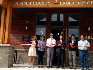 Photo of officials cutting a ribbon across the front of a building