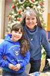 Photo of a woman standing with a girl in front of a Christmas tree.
