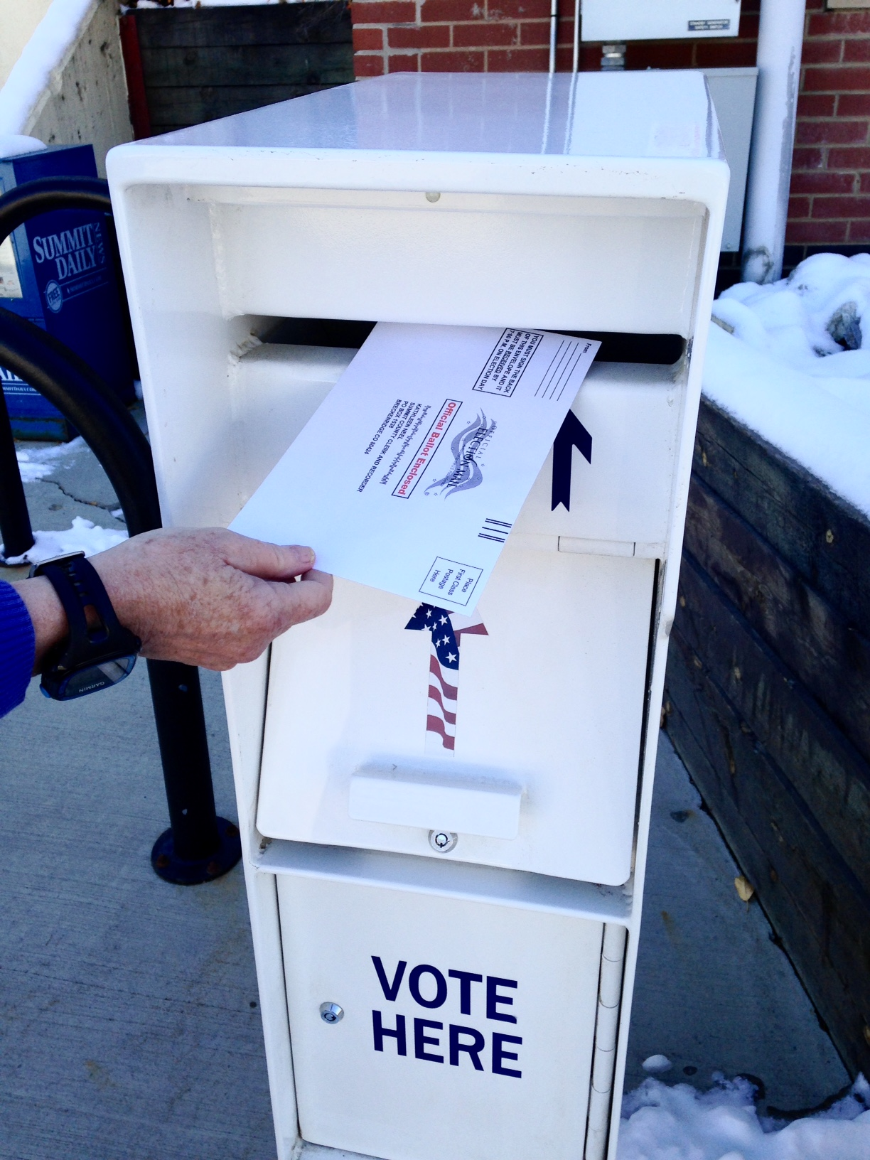 Photo of a hand dropping a ballot into a drop box.