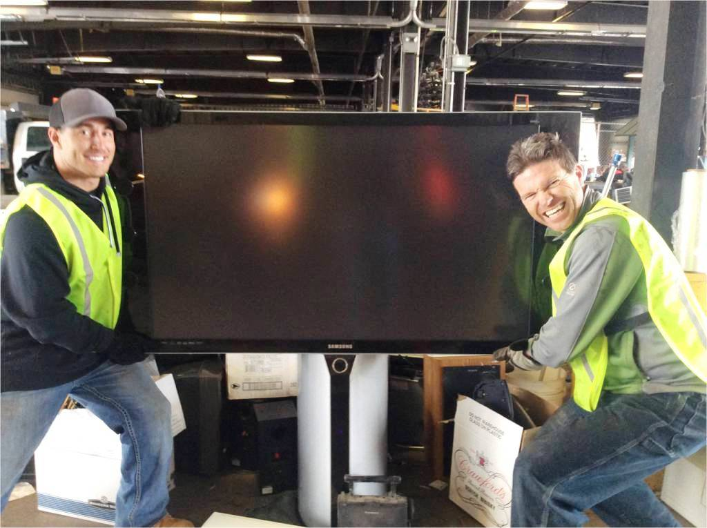 Photo of two men carrying a large TV.