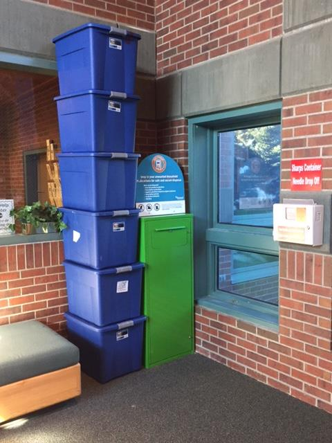 The six bins stacked next to the drop-box container at the Justice Center provide a visual for the containers required for 153 pounds of unused medications.