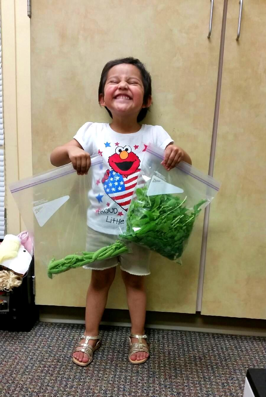 Photo of a smiling child holding a bag of vegetables.